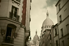 Montmartre in Paris, France. Old buildings in Montmartre (Paris, France) with Sacred Heart Basilica in the background Stock Images