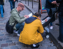 Montmartre street artist sketches baby in stroller while father amuses the baby. Street artist in Montmartre, Paris, crouches to work on a portrait sketch of a Stock Images