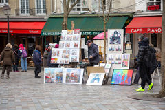 Montmartre street artists. PARIS, FRANCE - MARCH 3RD: Street artists display their work in a cobbled market square in Montmartre, 18th Arrondissement. On March Royalty Free Stock Photos