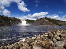Montmorency Falls. Scenic view of Montmorency Falls with Saint Lawrence river and rocky shoreline in foreground, Quebec, Canada stock photography