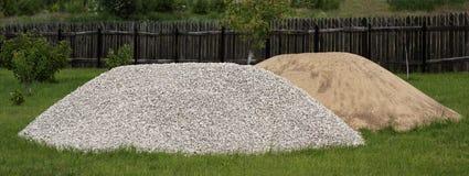 Montones de la arena y de piedras de macadán en la hierba Fotografía de archivo libre de regalías
