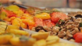 Montones de la comida asada a la parrilla en el mercado callejero Setas y verduras de la barbacoa: paprika, patatas con eneldo y  almacen de metraje de vídeo