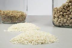 Montones de los granos del arroz delante de los garbanzos y de las lentejas imagenes de archivo