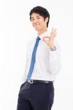 Montrant à pouce le jeune homme asiatique d'affaires. Images libres de droits