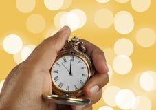 Montre antique d'or de concept de compte à rebours de nouvelle année dans une main Photos stock