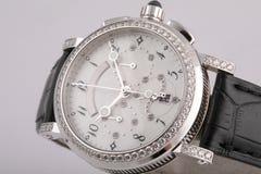 Montre argentée femelle avec un cadran blanc, dans le sens horaire argenté, chronographe, chronomètre, encadrement des pierres, a image stock