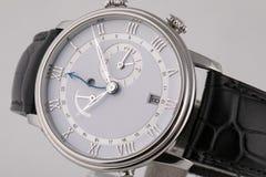 Montre-bracelet argentée avec le cadran blanc, dans le sens horaire argenté, chronomètre et chronographe sur le bracelet en cuir  photos stock
