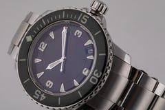 Montre-bracelet argentée avec le cadran bleu, dans le sens horaire argenté, chronographe, sur la courroie en métal sur le fond bl photographie stock libre de droits
