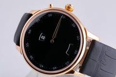 Montre-bracelet d'or avec le cadran noir, dans le sens horaire noir, chronographe sur le bracelet en cuir noir sur le fond blanc image stock