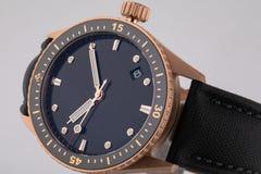 Montre-bracelet d'or avec le cadran noir, phosphore dans le sens horaire avec le chronographe sur la courroie noire de tissu d'is photos libres de droits