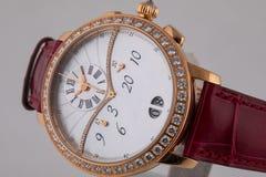 Montre-bracelet d'or femelle avec le cadran blanc, dans le sens horaire d'or avec le chronographe sur le bracelet en cuir de Bour photos stock