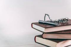 Montre-bracelet et stylo sur la pile des livres sur la table images libres de droits