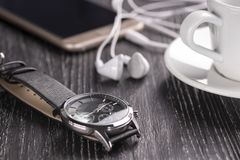 Montre-bracelet et téléphone portable avec des écouteurs et une tasse de café sur une table en bois foncée photos stock