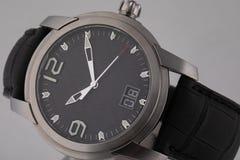 Montre-bracelet grise avec le cadran noir, l'argent dans le sens horaire, et le chronographe sur le bracelet en cuir noir d'isole photos libres de droits