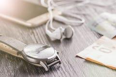 Montre-bracelet, téléphone portable avec des écouteurs et bloc-notes sur le vieux bureau foncé de bureau Est tout près l'euro not photographie stock
