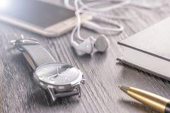 Montre-bracelet, téléphone portable avec des écouteurs et un bloc-notes avec un stylo sur un vieux bureau foncé de bureau photographie stock libre de droits