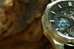 Montre de chronographe mise près du fond en bois photographie stock libre de droits