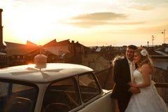 Montre de jeunes mariés le coucher du soleil se tenant sur le toit photos libres de droits