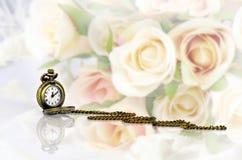 Montre de poche avec le bouquet rose sur le fond en pastel de ton Photos stock