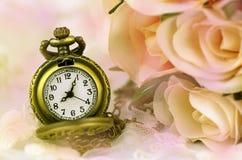 Montre de poche avec le bouquet rose sur le fond en pastel de ton Photo stock