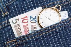 Montre de poche dans votre pantalon et jeans avec l'euro d'argent. Image stock