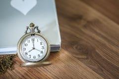 Montre de poche de luxe au-dessus du livre sur la table en bois avec l'espace de copie Photo libre de droits