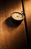 Montre de poche de vintage avec l'ombre sur le fond en bois sous le faisceau de lumière photos libres de droits