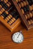 Montre de poche sur la table par l'abaque en bois Photo stock