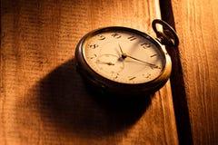Montre de poche de vintage avec l'ombre sur le fond en bois sous le faisceau de lumière photo libre de droits