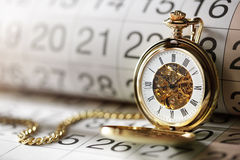 Montre et calendrier de poche d'or Photographie stock libre de droits