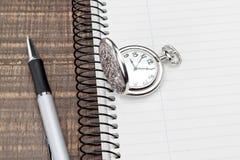 Montre et stylo de poche sur le carnet dans une cellule. Photographie stock