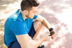 Montre intelligente de Syncing de taqueur avec Smartphone tout en se reposant en parc image stock