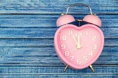 Montre rose de coeur sur le fond en bois bleu Photo stock