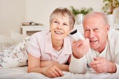 Montre TV d'aînés utilisant à télécommande Images stock