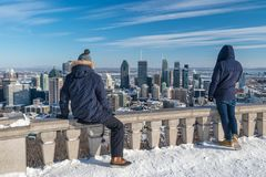 Tourists looking at Montreal Skyline from Kondiaronk belvedere in winter. Montreal, CA - 8 February 2018: Tourists looking at Montreal Skyline from Kondiaronk royalty free stock images