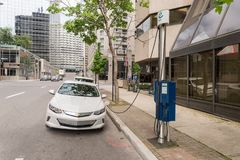 Electric car plugged into an EV charging station stock photo