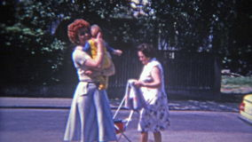 MONTREAL, CANADA 1973: Fashionable French Canadian mom taking baby from oldnanny.