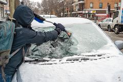 Man cleaning car windshield from ice stock images