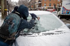 Man cleaning car windshield from ice with scraper tool royalty free stock images