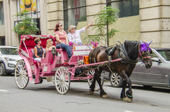 Montreal, Canada - July 26, 2014: Group of people taking tour in pink horse carriage in city Stock Photo