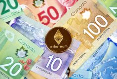 Ethereum cryptocurrency coin. MONTREAL, CANADA - MARCH 10, 2018: Ethereum cryptocurrency coin and logo on canadian bank notes Stock Photos