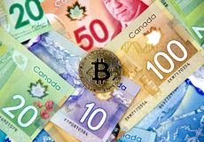 Gold bitcoin coin. MONTREAL, CANADA - MARCH 10, 2018: Gold bitcoin cryptocurrency on canadian bank notes Royalty Free Stock Photography