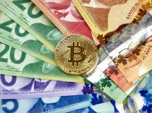 Gold bitcoin coin. MONTREAL, CANADA - MARCH 10, 2018: Gold bitcoin cryptocurrency on canadian bank notes Royalty Free Stock Photo