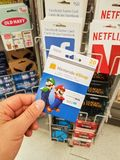 A hand holding a Nintendo gift card. MONTREAL, CANADA - MARCH 31, 2018 : A hand holding a Nintendo gift card. Nintendo eShop is a digital distribution service Stock Image