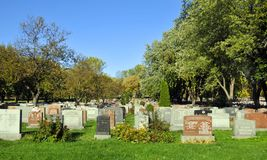Graves in Notre-Dame-des-Neiges Cemetery. MONTREAL CANADA OCTOBER 11 2015: Graves in Notre-Dame-des-Neiges Cemetery with colorful autumn trees. Is the largest royalty free stock photography