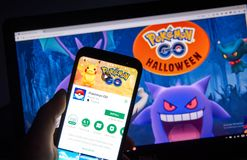 Pokemon Go Home android app over Halloween page. MONTREAL, CANADA - OCTOBER 20, 2017: Pokemon GO android app on Samsung S8 over Pokemon Go Home page introducing royalty free stock image