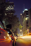 Montreal city street at night. A view of a row of cars parked along a Montreal city street at night with city buildings in the distance royalty free stock images