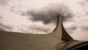 Montreal Olympic Stadium. Montreal Olympic Stadium from below with dark clouds royalty free stock photos