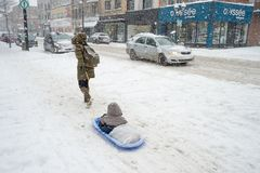 A mother is driving sledge with kid, during snowstorm. royalty free stock photos