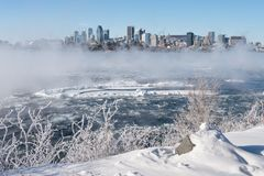 Montreal Skyline and St. Lawrence River in winter. Montreal, CA - 1 January 2018: Montreal Skyline in winter as ice fog rises off the St. Lawrence River stock photos